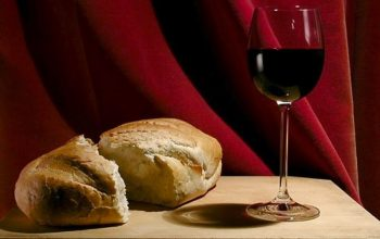 An image of a wine filled in a glass and piece of bread that placed on the table.